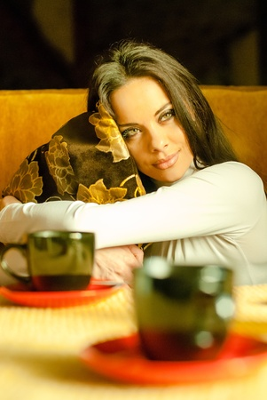Beautiful young woman with a cup of tea at a cafe photo