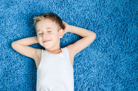 Happy boy smiling kid on blue carpet in living room at home Imagens