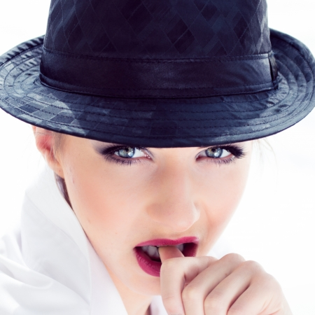 gracefully: Coseup portrait of a beautiful elegant young woman with black hat bitting finger on white background