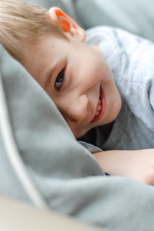 Happy boy smiling kid hiding in bed at home Stock Photo - 18711441