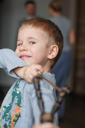 Happy kid preschooler boy playing in living room at home with slingshot or tweaker Stock Photo - 18735217