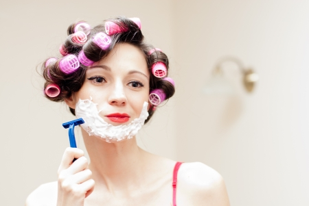 Beautiful funny young woman shaving with foam   razor her face Stockfoto