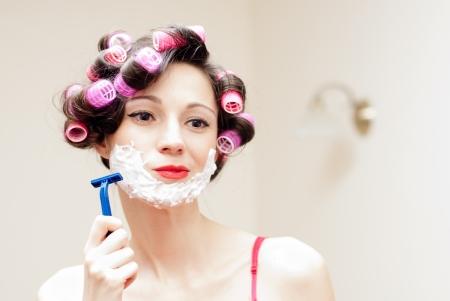 Beautiful funny young woman shaving with foam   razor her face Standard-Bild