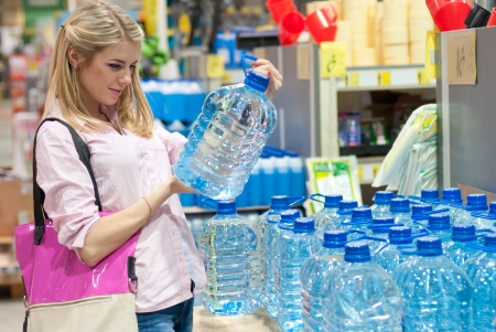 Pretty blonde girl in shop selecting clean water photo