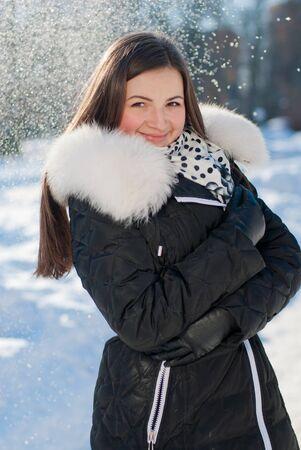 schöne junge glücklich lächelnde Frau auf dem Schnee im Freien Hintergrund Standard-Bild