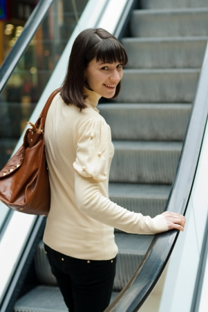 A happy smiling beautiful young woman on escalator at shopping center photo