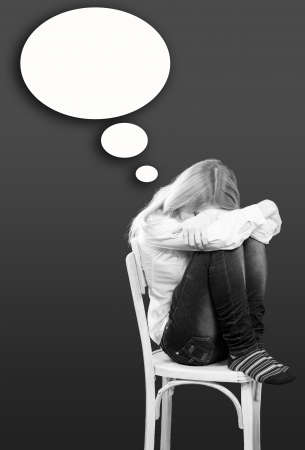 Young woman sitting depressed on chair and crying face covered with hands photo