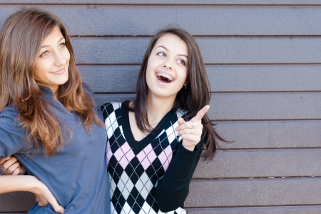 Two Teen young women happy laughing pointing to copyspace, dressed for spring or autumn outdoors photo