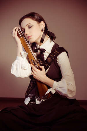 Steampunk pretty young victorian Woman With Pistol indoors photo
