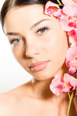 Portrait of a beautiful young woman face with perfect skin & lips, pink flowers around face. photo