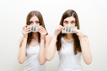 voiceless: Portrait of a two beautiful teen girls showing silenced by money. Studio shot on a white background