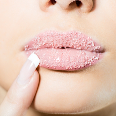 Woman's sweet sugary lips with finger photo