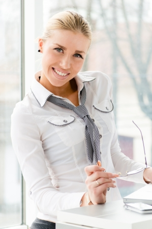 Young happy beautiful business woman smiling and holding glasses in office by window and computer Archivio Fotografico