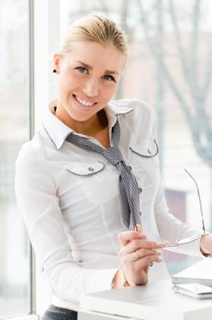 Giovani felice bella donna d'affari sorridente e detenzione di occhiali in carica da finestra e il computer