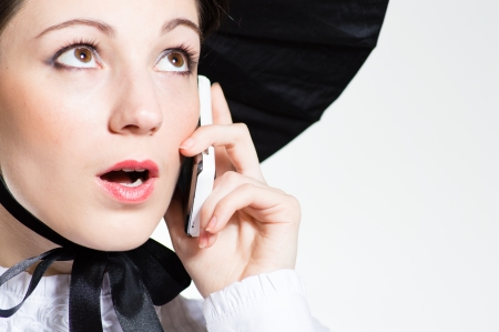 Young surprised woman in huge black hat with mobile phone looking closeup portrait on copyspace over white background Stock Photo - 19455360