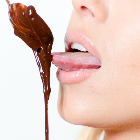 Closeup on tongue licking hot melting chocolate photo