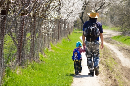 Father and son walking together on spring blooming path photo
