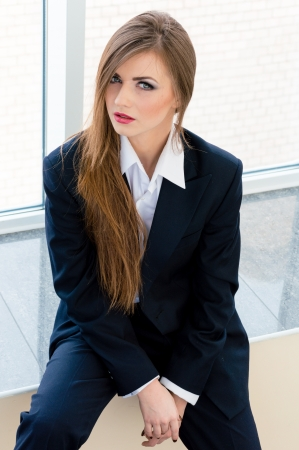 bossy: Young business woman looking bossy wearing mans suit in office Stock Photo