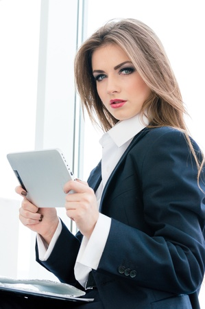 Portrait of successful confident young business woman in man suit using tablet PC photo