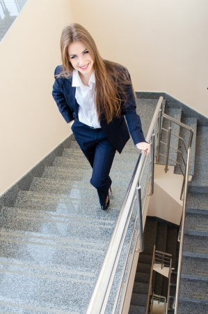 Young business woman looking bossy wearing man's suit walking up stairs Standard-Bild