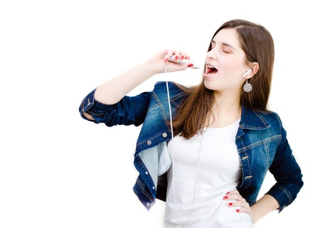 Young happy teenage girl in jeans jacket singing with music player on white background copyspace photo