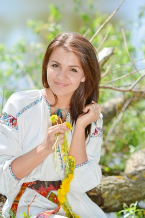 Young happy woman in traditional ukrainian dress making flower garland Stock Photo - 19730737