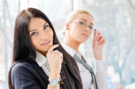Happy giovani donne d'affari sorridente e uno con gli occhiali in ufficio con finestra e il computer