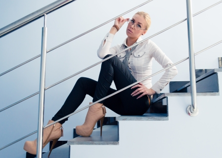 Young business fashion woman sitting on stairs photo