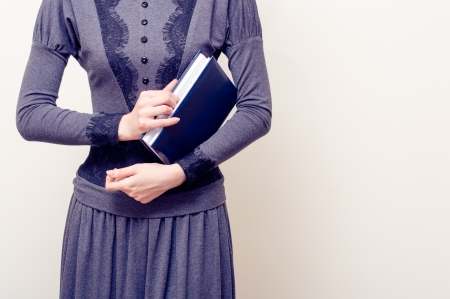 Young beautiful woman in gray vintage dress holding bible over light background copyspace Stock Photo - 20103763