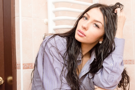 Young beautiful woman wearing man shirt with wet long dark hair photo