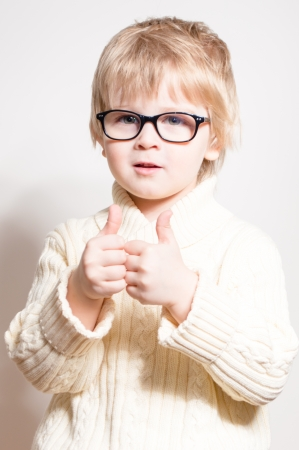 Little boy wearing glasses and showing thumbs up over white studio background photo