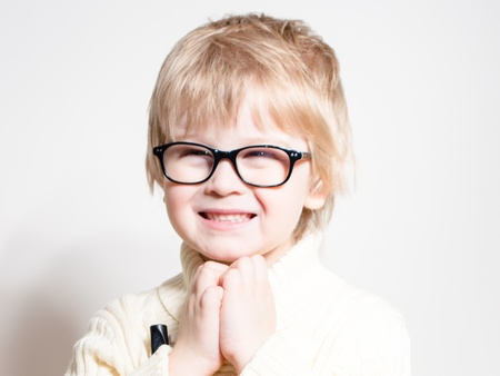 Little boy wearing glasses and smiling happy over white studio background photo