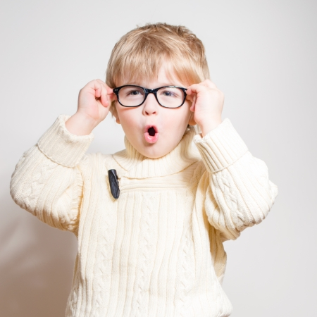 Little boy wearing glasses and looking surprised over white studio background photo