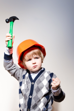 Little boy in builder helmet holding toy hammer up and showing fist photo