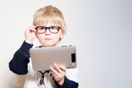 Little boy in eye glasses reading or playing on tablet pc in studio photo