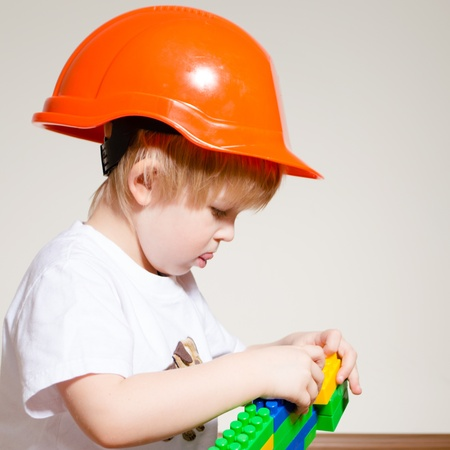 Little boy in orange builder helmet playing with constructor in studio over white background photo