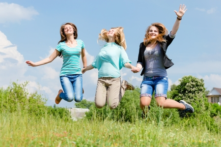 Three happy teen girls friends jumping high on green lawn against blue sky photo