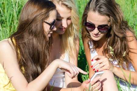 Three happy teen girl friends looking on mobile phone while sitting on green lawn on summer day photo