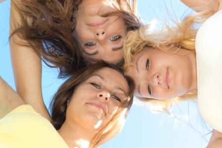 joyfull: Three happy teen girls friends looking down against blue sky background Stock Photo