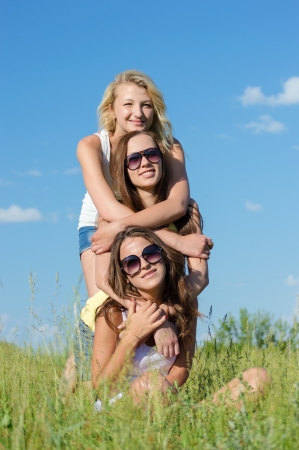 friend hug: Three happy teen girls sitting on green grass and embracing against blue sky on bright summer day