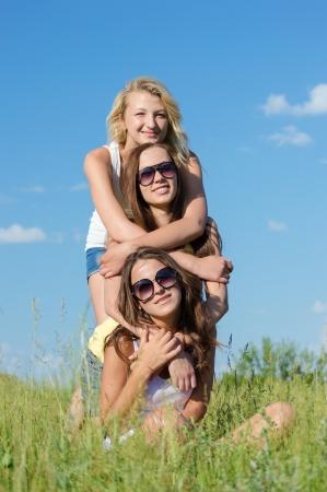 mejores amigas: Tres chicas adolescentes felices que se sientan en la hierba verde y abrazan contra el cielo azul en un d�a brillante de verano