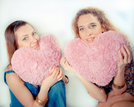 Two beautiful young girls talking privately on white background photo