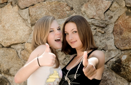 Two happy teenage girls showing thumbs up outdoors photo