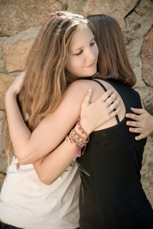 Teenage girl comforting crying friend with warm hug photo