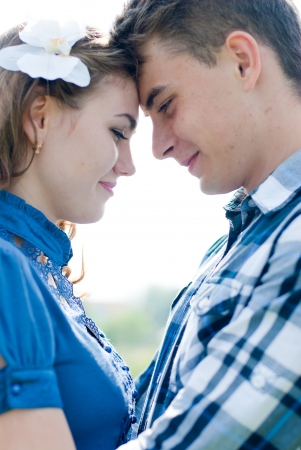 Happy teenage couple boy and girl embracing over blue sky background