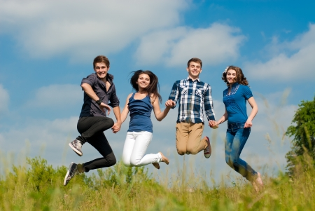 Four happy teenage friends boys and girls jumping high in blue sky photo