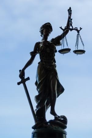 justitia: Femida diosa estatua de bronce que sostiene las escalas sobre el cielo azul Foto de archivo