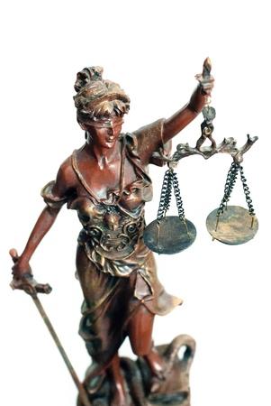 sword act: Femida bronze goddess statue holding scales over white background