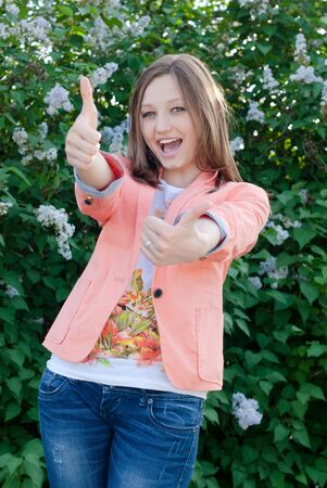 happy young woman showing thumbs up on the summer outdoors background photo