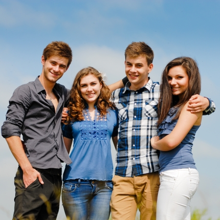 Four happy teenage friends boys and girls outdoors against blue sky background